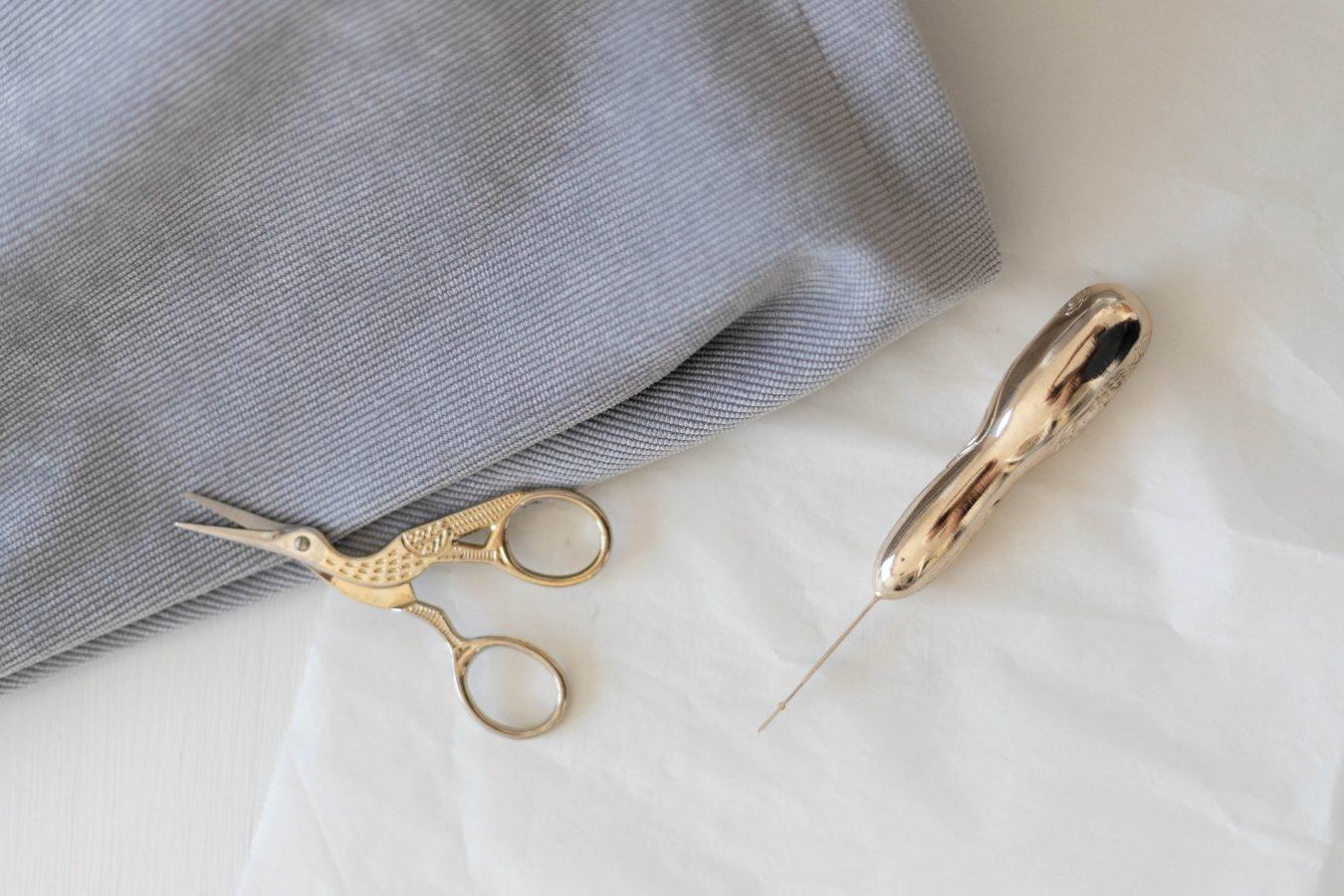 Nähutensilien vor grauem Stoff, goldene kleine Schere, Nahtauftrenner in Gold